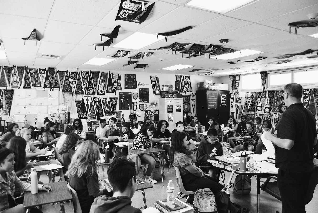Numerous college pennants hang in IB English HL Teacher Eric Helle's classroom as he instructs his seventh period Speech and Theater course.  Helle is among the BVH staff members who are part of the College-Going Culture Committee.