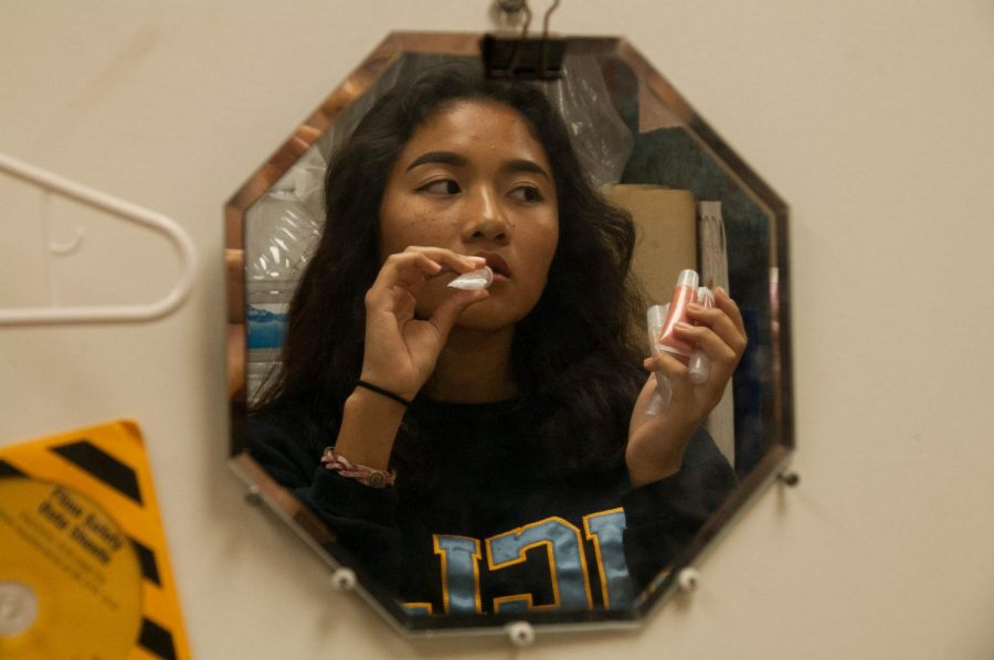 """Edelina Bagaporo demonstrates putting on her homemade lip gloss that she markets at school under her brand """"intrntgrl.cosmetics."""""""