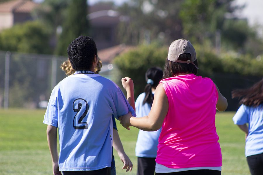 A mother pulls her of a child from San Ysidro High School (#2), along with her to the opposing side of the field.