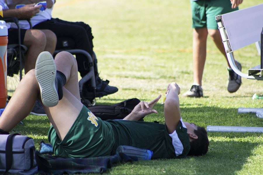 A student from Mar Vista High School lounges at the sidelines waiting for the game taking place to finish.