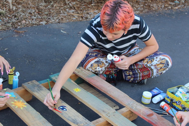 Lilian Landre paints the wooden pallets that hold the succulents