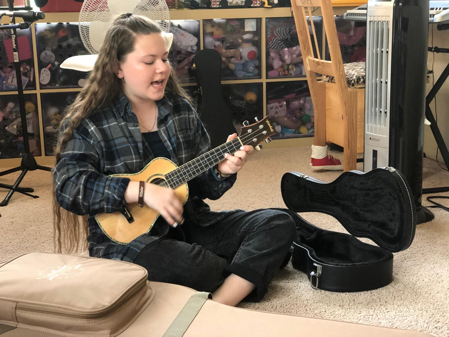 """Bonita Vista Middle school eighth grader, Kieler Muller sings, """"The Reason,"""" by Maddie Poppe while playing her ukulele. This room in her house is where she normally practices one of the four instruments she is self-taught in: guitar, piano, ukulele and trumpet."""