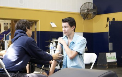 Member of the Sports Medicine club and volunteer senior Kevin Tang administers a blood pressure test on a student getting a sports physical.