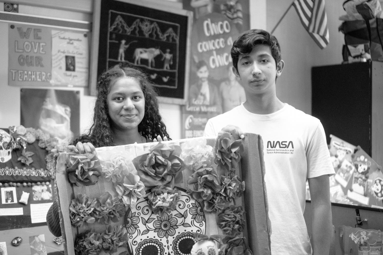 Noor Alramadan and Enrique Torres display a decorative piece from Spanish language teacher Maria De La Cruz's classroom. These pieces are put on display in preparation of Dia de los Muertos.