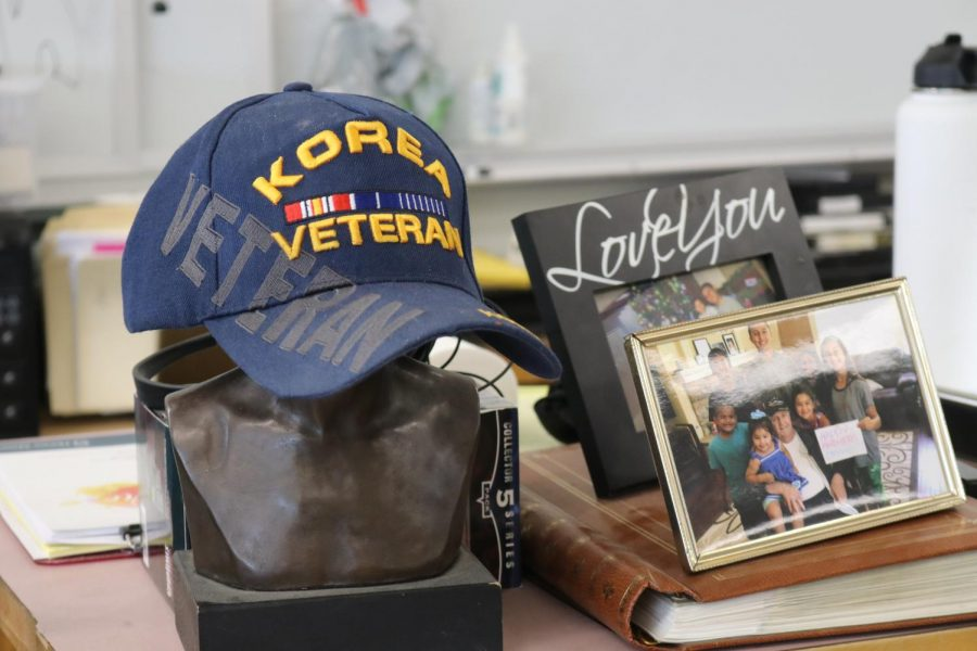 In his classroom at the end of the 200s buildings, Government and History teacher Frank Schneeman decorates his room with photos of his family members and a bust of George Washington. On Washington's head rests Schneemann's cap that references his service in the Korean War.