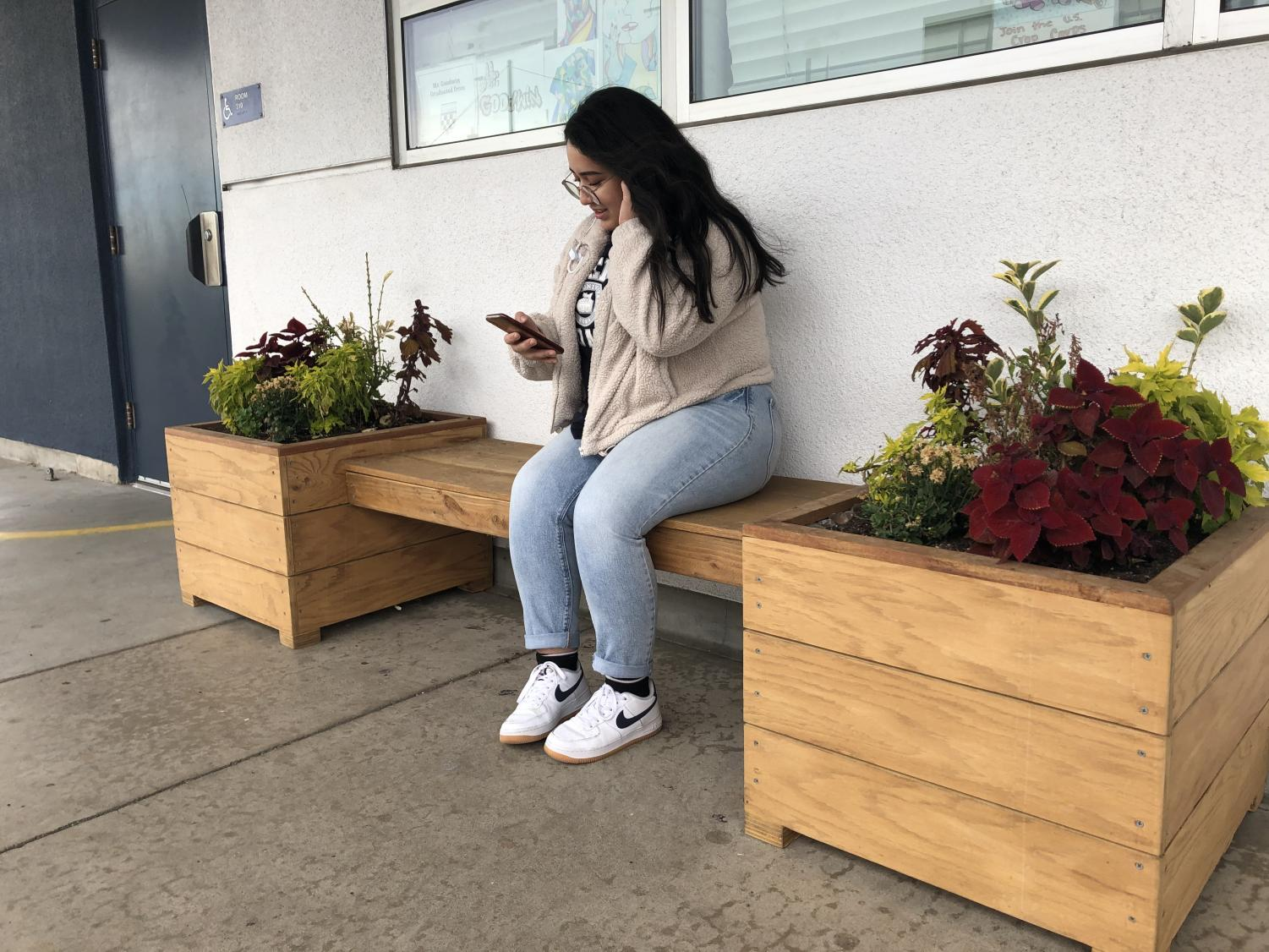 Senior Ruby Rodriguez sits on Green Team's newly installed benches outside AP Art History teacher James Goodwin's classroom on Monday, Dec. 2nd, 2019.