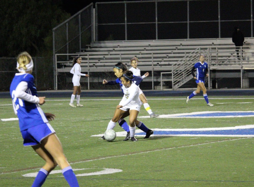 BVH player Ashley Escamilla (2) keeps the ball away from an Eastlake High School player during the Jan. 17 away game. Distributed throughout the field, other players  dressed in white and blue watched the fight for the ball.