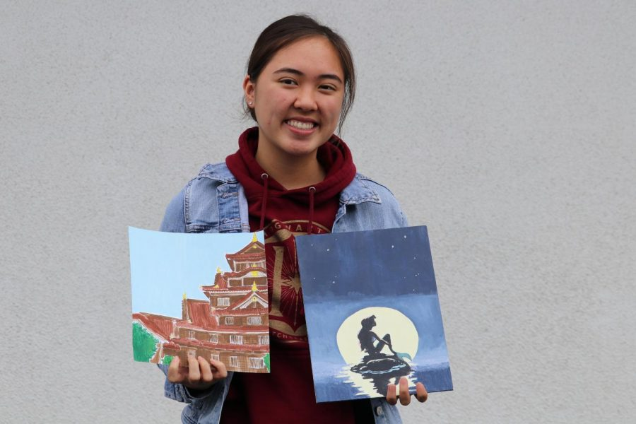Junior Ashley Ratcliff holds up two of her art pieces. On the left is a Japanese temple she saw a picture of online and the right is of Disney character Ariel.