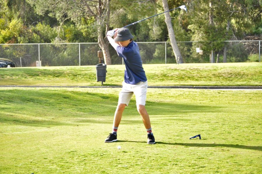 Junior+Jackson+Loughney+delivers+his+first+swing+at+the+first+hole.+Coach+Michael+Wegenka+and+players+spectate+quietly+from+behind.