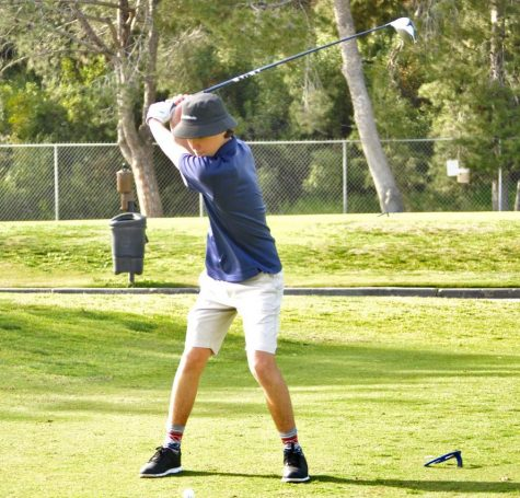 Junior Jackson Loughney delivers his first swing at the first hole. Coach Michael Wegenka and players spectate quietly from behind.