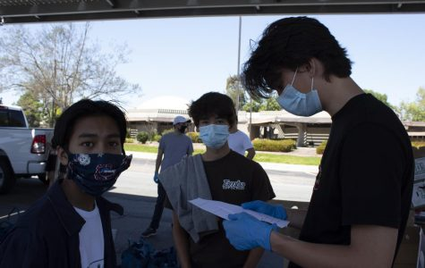 Juniors Daniel Boll (middle) and Aaron Pangilinan (middle) look up to the voice of one of the Courage to Call directors orders while Benjamin Conte (right) looks at his community service form. The students volunteered for the Courage to Call's food drive at Southwestern College.