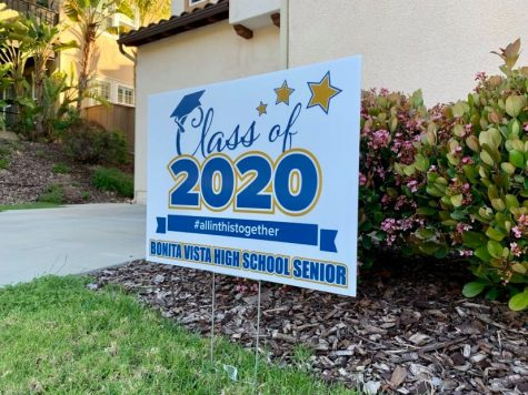 "In Chula Vista, a front lawn is adorned by a sign that reads ""Class of 2020 #allinthistogether Bonita Vista High School Senior"". Many seniors in San Diego County have purchased these signs from different sources in order to celebrate their graduation from high school."