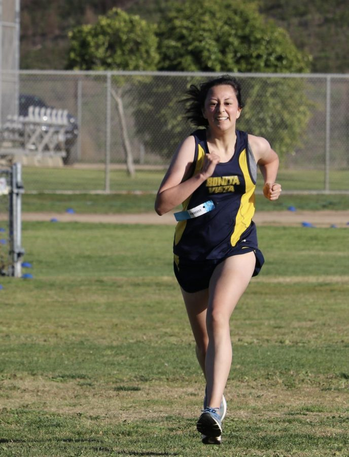Varsity cross country runner and junior Kiara Sandoval speeds up as she reaches the finish line. The race path was delineated with colored cones and white lines.