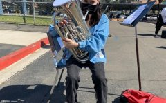 Club Blue member Alexis Garcia playing the euphonium through the specialized mask. Club Blue practices just outside the band room.