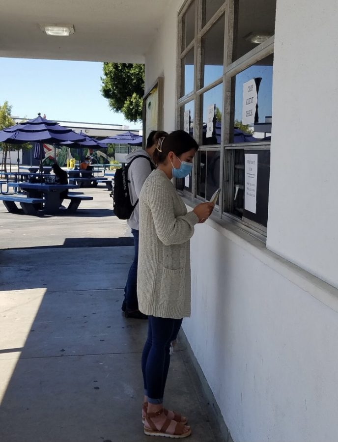 Senior Alexa Lazarit buys her Prom ticket from the ASB after school. Just as Lazarit must wear a mask while purchasing a ticket, she will also have to wear a mask at the event to follow the restrictions put in place given the current circumstances of the COVID-19 pandemic.