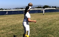 Senior Sophia Estrada received a pitch from fellow senior Nicole Hill. Their warm-up occured right before their game against Cathedral Catholic High School.