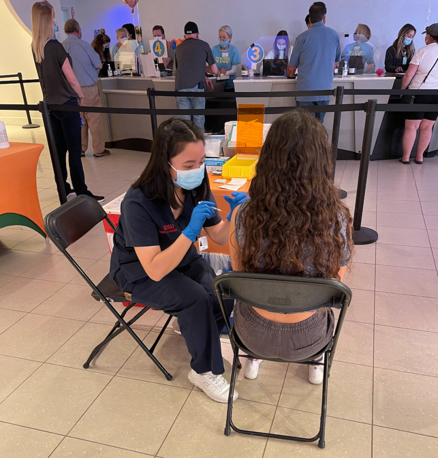 Junior Lourdes Castruita receives her first dose of the Pfizer Vaccine at the Grossmont Sharp Clinic. In the background other people wait to get their vaccines.