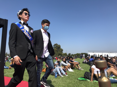 Homecoming Prince and senior Michael Dimapilis and English Accelerated, IB Literature Higher Level (HL) 1 and 2 teacher and escort Raymond Chhan make their way to the stage. The crowd cheers as Dimapilis takes his seat alongside the rest of the Homecoming court.